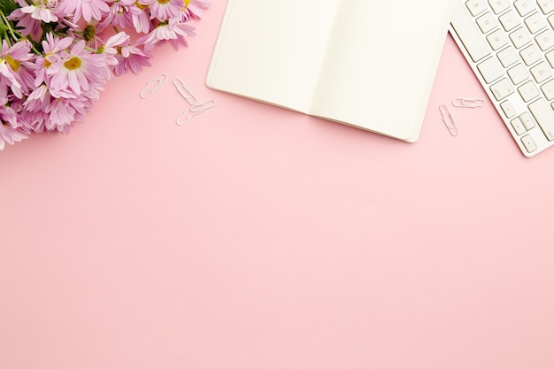 Werkend vrouwen roze bureau met leeg notitieboekje
