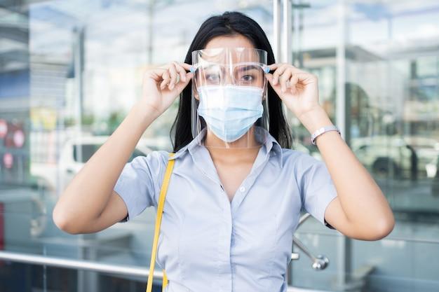 Werkende aziatische vrouw, hij draagt een masker en een gelaatsscherm ter bescherming tegen virussen.