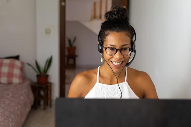 Werkende braziliaanse jonge vrouw in de slaapkamer. telemeeting. videoconferentie. afstandswerk. callcenter naar huis.