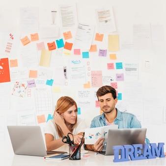 Werkende collega's die document op werkplaats met laptopskantoorbehoeften en naambord bekijken