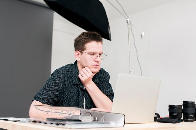 Werkende fotograafmens die zijn laptop bekijkt