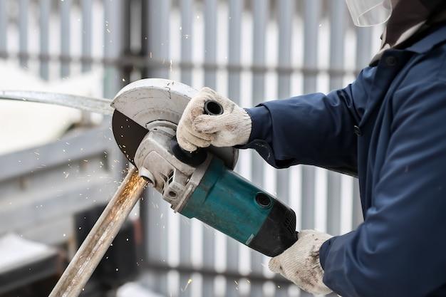 Werkende haakse slijper in de handen van een werknemer. handschoenen, metalen vonken. hoge kwaliteit foto