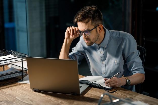 Werkende man kijken naar laptop met verwarring
