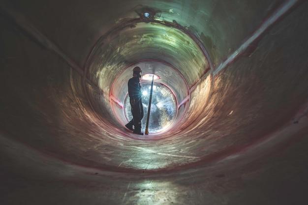Werkende mannelijke inspectielas ondergronds van de tunnel van tankapparatuur door de zaklamp aan de zijkant te gebruiken.