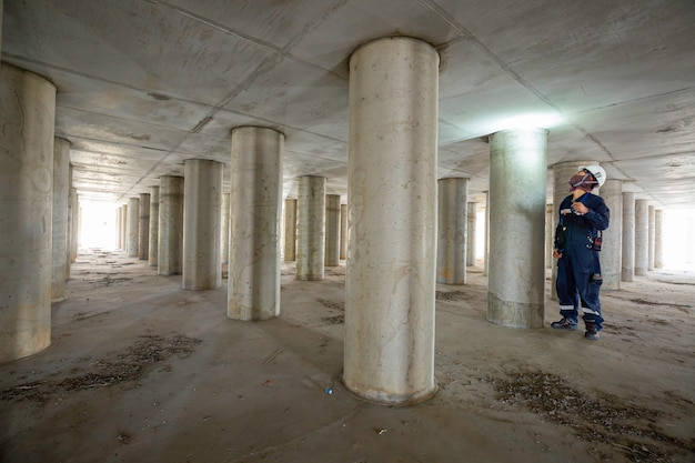 Werkende mannelijke inspectiepaal ondergronds van de tunnel van tankapparatuur door de zaklamp in de tank te gebruiken.