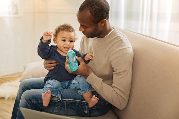 Werkende papa. aantrekkelijke gelukkig donkerogige bebaarde afro-amerikaanse man die lacht en zijn zoon op zijn schoot houdt terwijl hij aan het werk is op de laptop en een vel papier vasthoudt