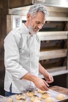 Werkende stemming. grijsharige bebaarde man in wit jasje besprenkelen broodjes met granen attent vrolijk