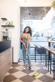 Werkende stemming. jonge mooie vrouw in denim overall en sneakers met mop doen schoonmaken in klein café in goed humeur