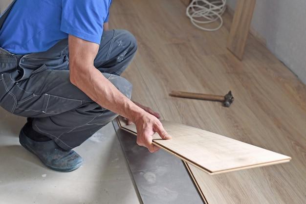 Werkende timmerman legt laminaatvloer in het appartement. het concept van werkende beroepen.