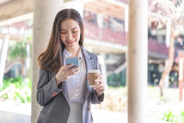 Werkende vrouw concept een jonge vrouwelijke manager die videoconferentie bijwoont en een kopje koffie vasthoudt.