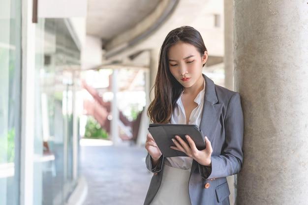 Werkende vrouw concept een jonge zakenvrouw die online werkt aan haar bedrijf met de handgreepapparaten, tablet, buiten de werkplek.