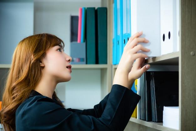 Werkende vrouw die boek zoekt van planken in bibliotheek