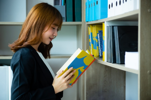 Werkende vrouw die een boek van planken in bibliotheek leest