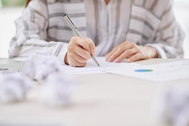 Werkende vrouw die op papier schrijft
