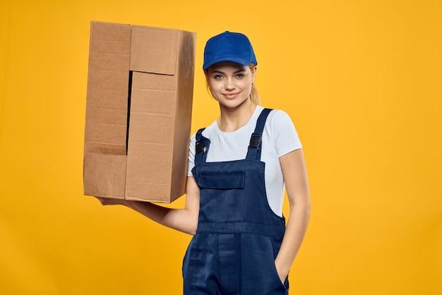 Werkende vrouw in eenvormige doos in handen koeriersdienst die gele achtergrond teruggeeft.