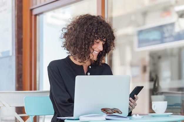 Werkende vrouw op een terras van een bar die mobiel bekijkt terwijl het werken met laptop en het hebben van een koffie.