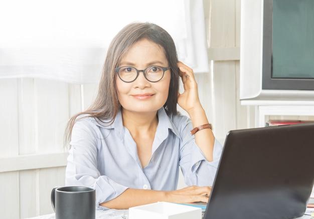 Werkende vrouwen. leeftijd 50. met werk en apparatuur.