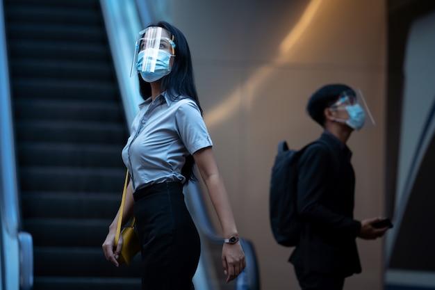 Werkende vrouwen zit ze in de metro. ze draagt een gelaatsscherm en een virusmasker.
