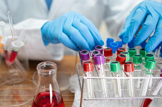 Werkende wetenschapper analyse met buis van microbiologisch monster