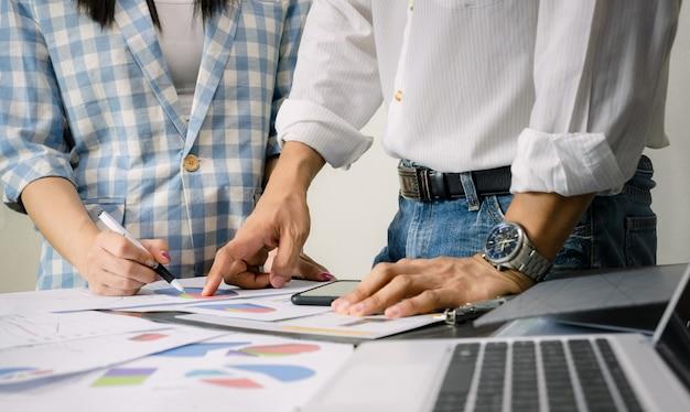Werkende zakelijke teamgrafiekanalyse op het bureau