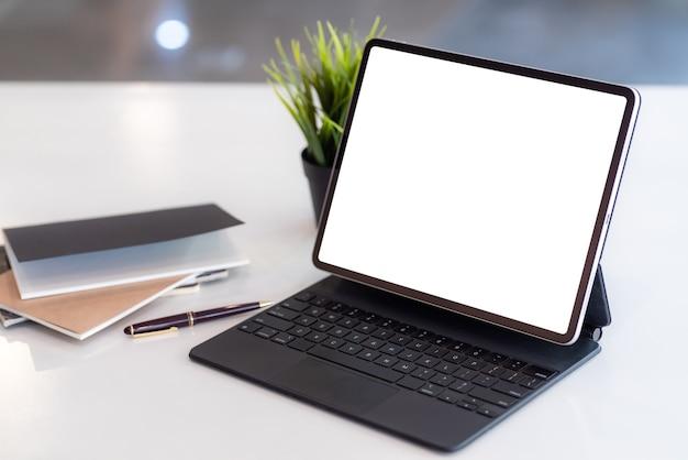 Werkgebied tablet leeg wit scherm met notitieblok een geplaatste tafel op kantoor.