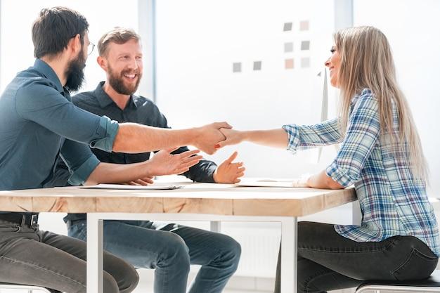 Werkgever handen schudden met een nieuwe werknemer tijdens interview