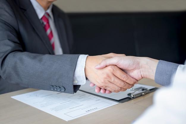 Werkgever in pak en nieuwe werknemer handen schudden na onderhandeling en sollicitatiegesprek