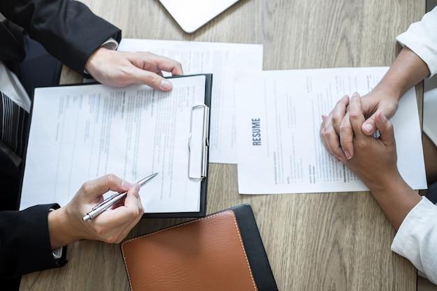 Werkgever of commissie houdt het lezen van een cv met praten tijdens over zijn profiel van kandidaat, werkgever in pak voert een sollicitatiegesprek, manager resource werkgelegenheid en wervingsconcept