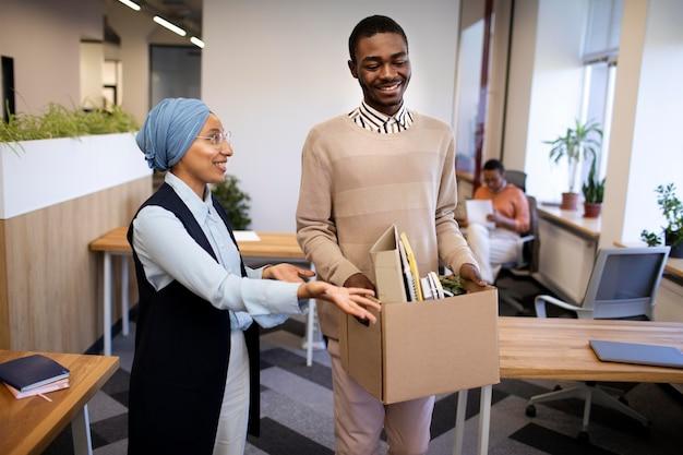 Werkgever toont man zijn bureau bij nieuwe baan terwijl hij een doos met spullen draagt