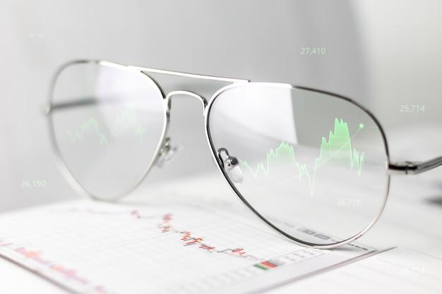 Werkglazen van zakenman tonen winst en grafiek van aandelen op optische lensscherm. virtual reality-glazen tonen het effect van een groeiende economie in termen van geld en economie.