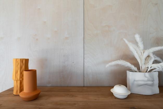 Werkhoek versierd met mosterdkleurige keramische vaas met kunstmatige plant in vaas op houten blad in natuurlijk lichtscène / appartement interieur kopie ruimte