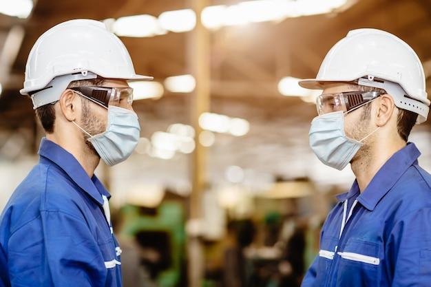 Werkkleding dragen gezichtsmasker staand op afstand tijdens het praten samen service in de fabriek om covid-19 virus luchtstofvervuiling te voorkomen en voor een goede gezondheid.