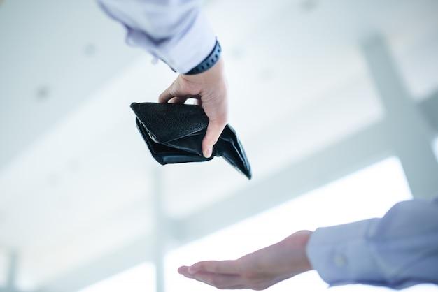 Werkloze man kijkt naar de portemonnee die geen geld in zijn zak heeft. hij is werkloos en wacht op een nieuwe baan. economische depressie en hopeloze crisisconcepten.