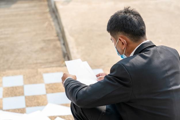 Werkloze man, zakenman ontslagen van baan zittend verdrietig buiten kantoor tot werkloosheid door de covid 19-ziektesituatie, coronavirus is een wereldwijde noodsituatie geworden.