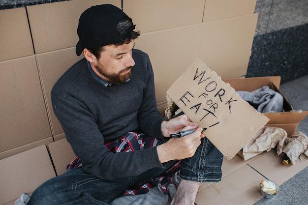 Werkloze man zit op de grond en schrijft werk voor eten op het stuk papier