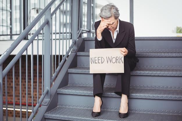 Werkloze zakenvrouw met behoefte werk plakkaat