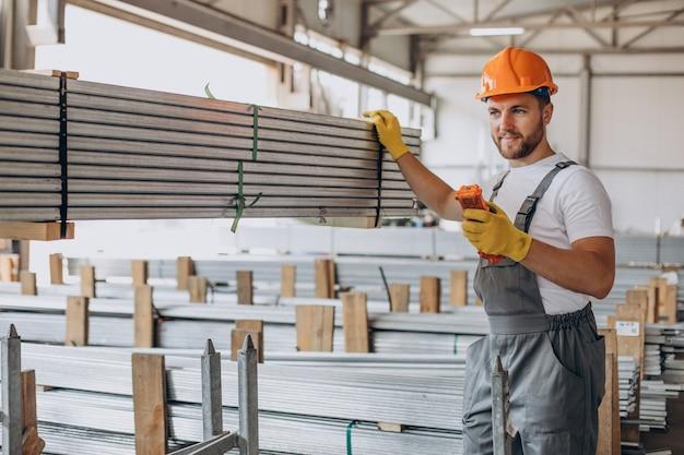 Werkman bij winkelhuis in oranje helm