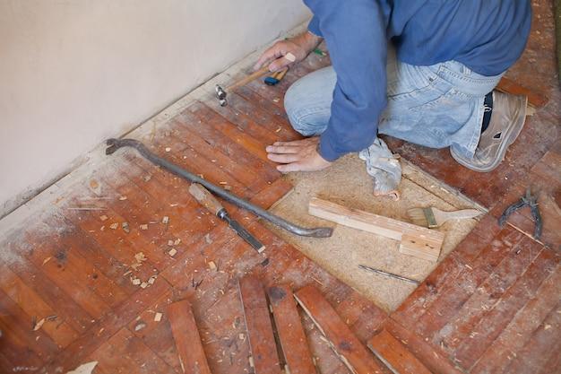 Werkman die oude vloer verwijdert. close-up van zijn gehandschoende handen