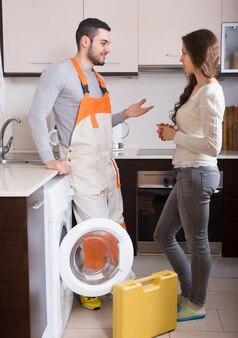 Werkman en cliënt dichtbij wasmachine