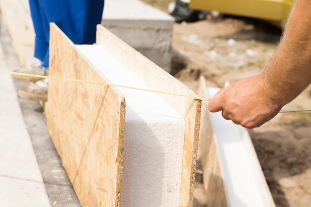 Werkman meet een prefab houten wandpaneel met isolatie op een bouwplaats alvorens het te installeren