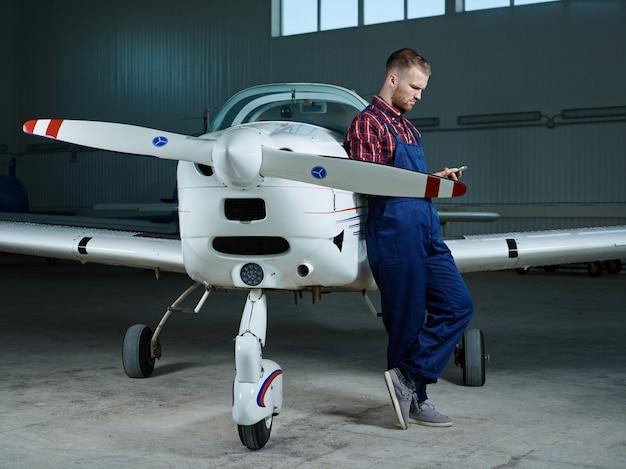 Werkman met smartphone en een vliegtuig
