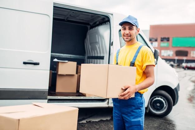 Werkman of koerier in uniform houdt kartonnen doos in handen, vrachtwagen met pakketten