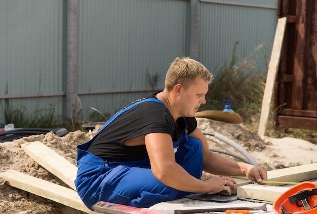 Werkman op een bouwplaats die een rechte hoekmeting uitvoert terwijl hij een houten geïsoleerde balk meet voordat hij deze snijdt en installeert
