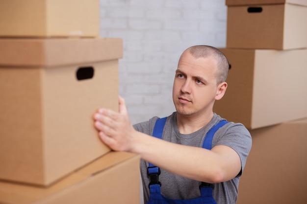 Werkmensenconcept - lader die grote doos van plank in magazijn neemt