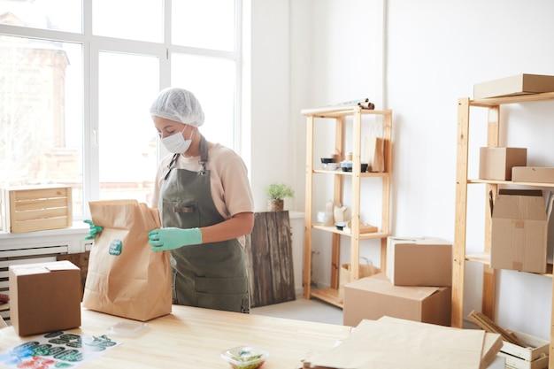 Werkneemster die beschermende kleding draagt tijdens het inpakken van bestellingen bij de bezorgservice voor eten