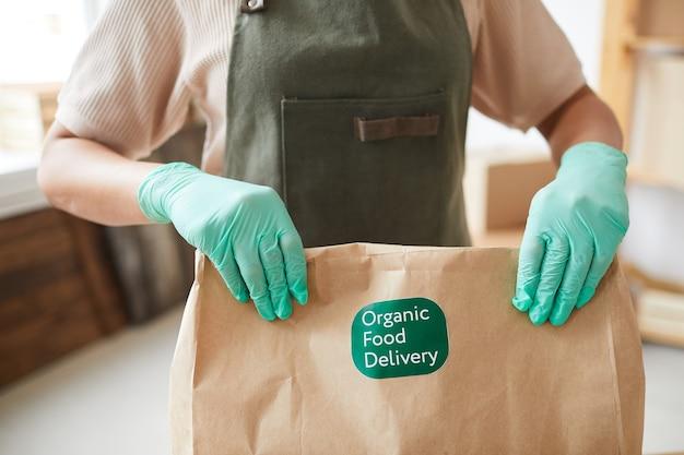 Werkneemster die handschoenen draagt en ambachtelijke papieren zak vasthoudt tijdens het verpakken van bestellingen bij de bezorgservice voor eten