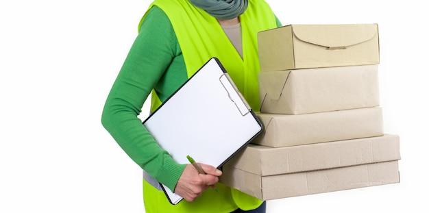 Werkneemster in een groen vest dat zich dichtbij heel wat document dozen met lege orde bevindt, leveringsconcept.