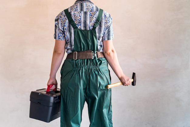 Werkneemster met gereedschapskist en hamer