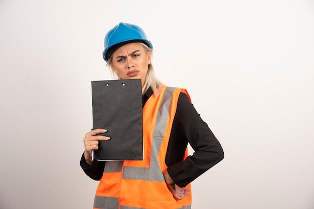 Werkneemster met klembord poseren met ontevreden blik. hoge kwaliteit foto