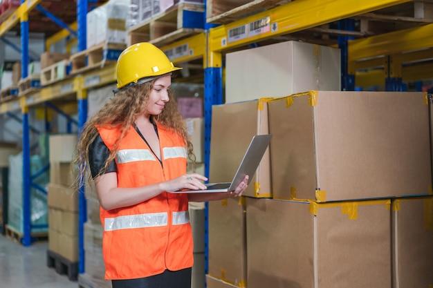 Werkneemster met laptop producten in voorraad in magazijn fabriek controleren